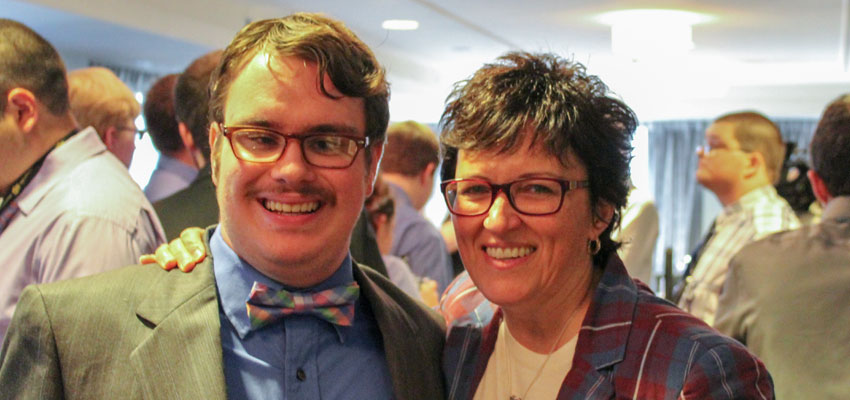 A man, dressed professionally, with a visual impairment standing next to a woman with glasses and a plaid blazer.