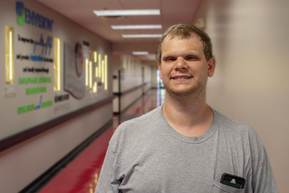 Chad Morrison, Envision employee who is blind, wearing a gray t-shirt standing in a hallway.