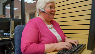 Woman with a visual impairment in a call center talking with a customer while wearing a headset and typing on a computer keyboard.