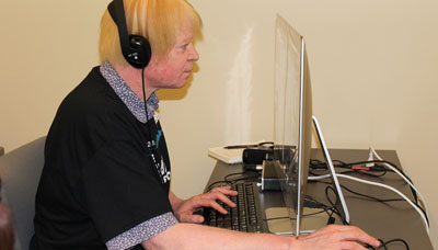 A man with a visual impairment in a call center talking with a customer while wearing a headset and typing on a computer keyboard.